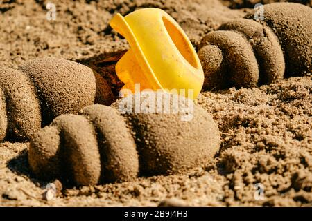 Used yellow toy boat lying upside down between sand shells on the sandy ground in the sun. Seen in Germany in March.