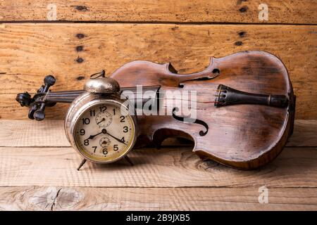 Antique clock and old violin over vintage wooden table - selective focus, copy space Stock Photo