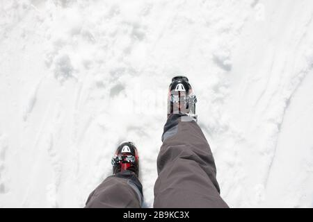 Skier legs with black pants and his red ski boots walking on snow. Wintersport concept - Stock Photo