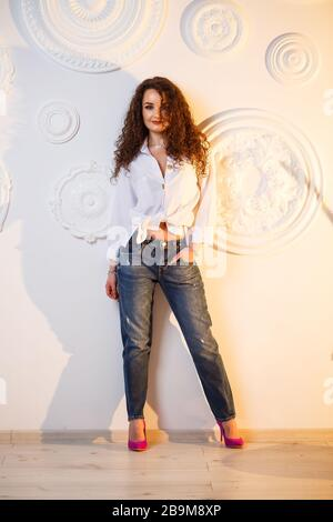 Beautiful young girl model with curls posing. She is wearing a white shirt and jeans.