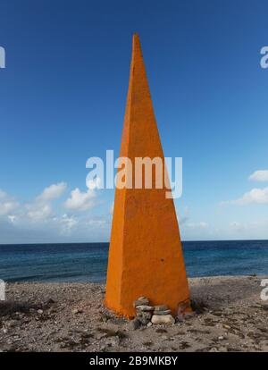 Red obelisk a historical marker for shipa to pick up their salt shipment, Bonaire, Caribbean - Stock Photo