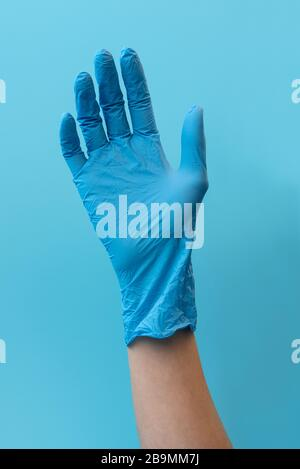 Hand wearing on blue latex gloves on blue background.  Flu, illness, pandemic and protection concept - Stock Photo