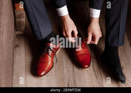 groom tied the laces on the shoes close up. business man is hanging shoes indoor in hotel room. mans hands and pair of leather men's shoes. meeting of - Stock Photo