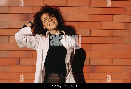 Curly haired caucasian woman posing outside on a stone wall while wearing eyeglasses and a nice white shirt