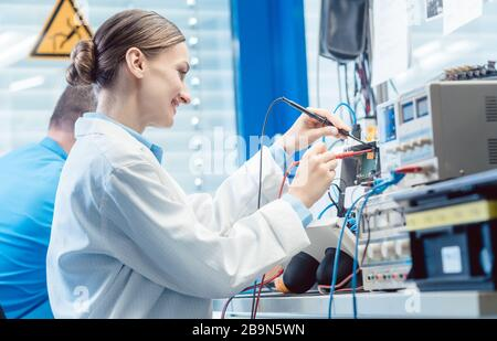 Team of engineers testing and measuring an electronic product in the lab - Stock Photo