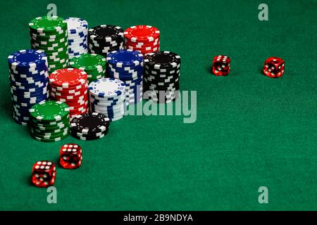 Large copy writing space with betting chips and 4 translucent red casino style dice on a green felt playing surface.  Vivid colors and contrast on the - Stock Photo