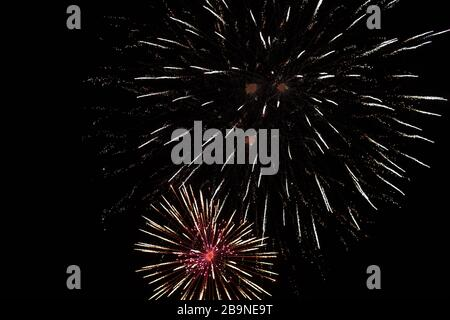 Brightly colorful fireworks and salute of various colors in the night sky background. selective focus - Stock Photo