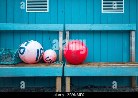 Outdoor still life - marking buoys and crab trap on wooden blue bench by the costal house in Scotland - Stock Photo