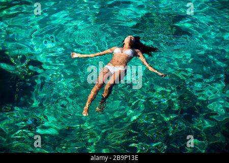 Healthy woman floats on her back at Black Rock, Ka'anapali, Maui, Hawaii. - Stock Photo