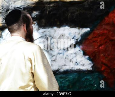 Anti Zionist Jewish man walking by a painted Palestinian flag in the super religious neighborhood of Mea Shearim in Jerusalem. - Stock Photo