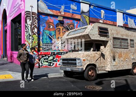 Couple walking in front of a camouflage RV parked in front of a colorful mural, Mission District, San Francisco, California, United States, color - Stock Photo