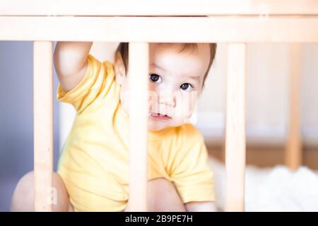 Cute baby sitting in cot looking across the room through the wooden frame. She is afraid of something. baby hide in crib - Stock Photo