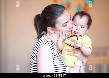 Beautiful young mother kissing and pampering her baby. mixed race kazakh