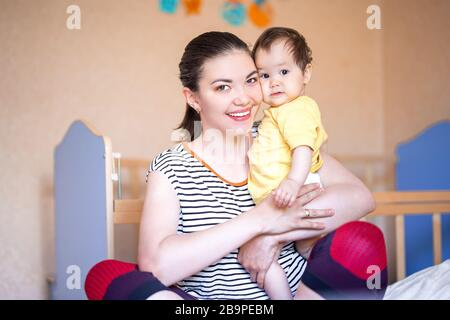 happy mother having fun with baby girl dark-haired mixed race kazakh and german caucasian russian - Stock Photo
