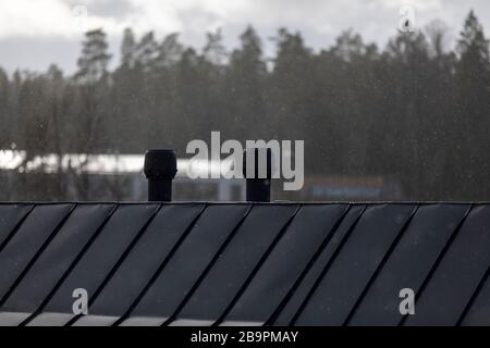 Light snowfall and rooftops in Finnish spring with no people - Stock Photo