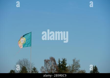 Damaged or ragged Portuguese flag, waving in the blowing wind in allotment garden colony Urdorf, Switzerland - Stock Photo