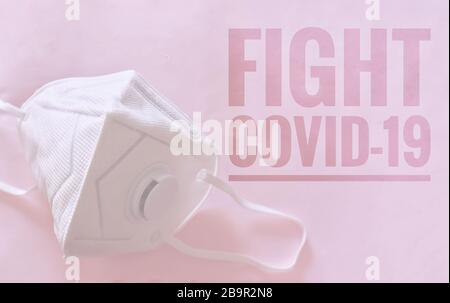 N95 mask against a pink background with the words 'Fight Covid-19' to raise awareness about the outbreak - Stock Photo