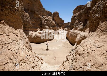 Tourist inside Sesriem Canyon, Namib Naukluft Park, Namibia - Stock Photo