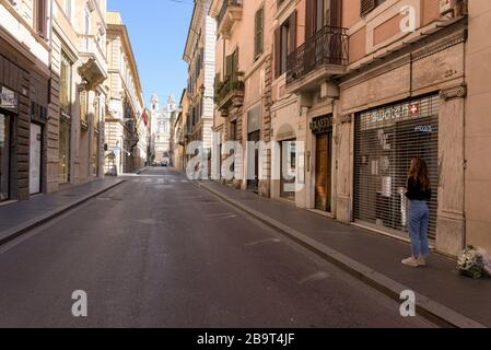 ROME, ITALY - 12 March 2020: A woman stands in front of closed shops in Via dei Condotti, next to the Spanish Steps, Rome, Italy. One must justify the
