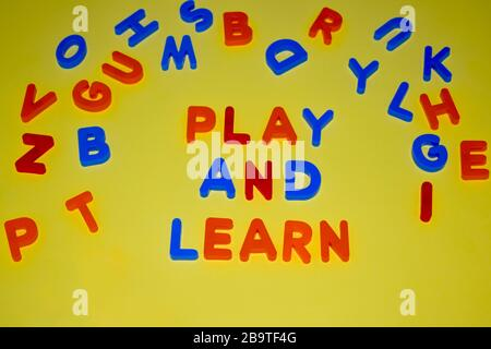 Play and learn words written with different colored letter blocks which are scattered on a yellow background - Stock Photo