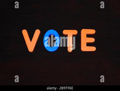 Vote word written with different colored letter blocks arranged on a dark background