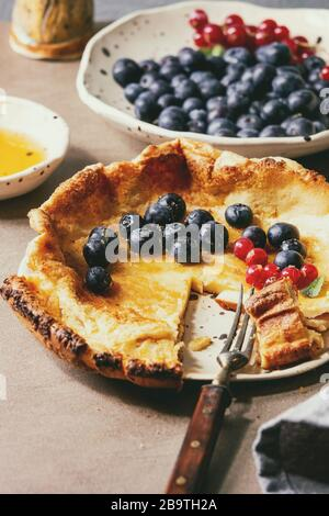 Started eaten fresh baked Dutch baby pancake in ceramic plate with blackberry and red currant berries, bowl of honey, jug of cream, vintage cutlery ov - Stock Photo