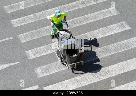 Street sweeper pushing a cart on crosswalk. Public cleaning concept - Stock Photo