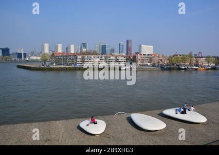 From the south of Rotterdam overlooking the Maas River the the modern city centre with in the foreground huge art bollards and the Noordereiland - Stock Photo