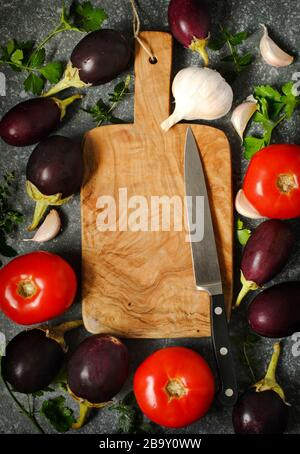 Tomatoes, eggplants and garlic around wooden cutting board  on stone texture background. Stock Photo