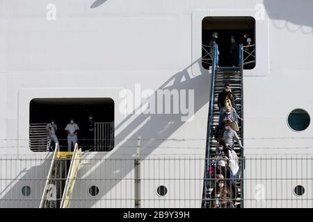 Lisbon. 24th Mar, 2020.  Passengers wearing protective masks disembark from MSC Fantasia cruise ship at the port in Lisbon, Portugal, March 24, 2020. The Portuguese authorities said on Sunday that all the passengers who arrived in Lisbon aboard a cruise ship will have to undergo screening tests for the COVID-19, Lusa News Agency reported. According to a statement from the Ministry of Internal Administration (MAI), the cruise ship MSC Fantasia from Brazil arrived in Lisbon early on Sunday with 1,338 passengers, of which 27 are Portuguese citizens.  - Stock Photo