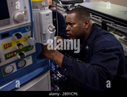 Los Angeles, California, USA. 25th Mar, 2020. Hospital Corpsman 2nd Class Alton Gibbs, from Dothan, Ala., reconnects hoses to an anesthesia machine aboard the Military Sealift Command hospital ship USNS Mercy (T-AH 19) on March 24, 2020. Mercy deployed in support of the nation's COVID-19 response efforts, and will serve as a referral hospital for non-COVID-19 patients currently admitted to shore-based hospitals. This allows shore base hospitals to focus their efforts on COVID-19 cases. One of the Department of Defense's missions is Defense Support of Civil Authorities. DoD is supporting the Fe - Stock Photo