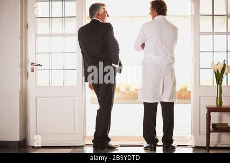 Rear view of two male doctors talking. - Stock Photo