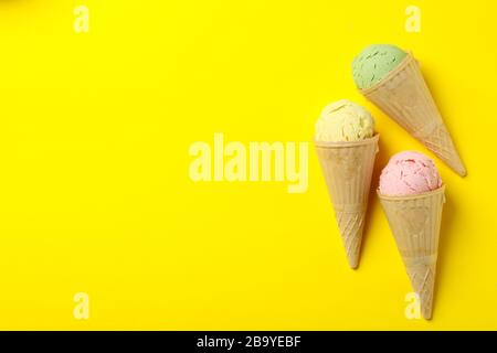 Ice cream in waffle on yellow background, space for text Stock Photo