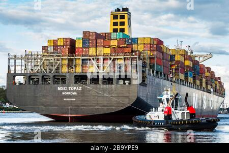 MSC Topaz Container Ship is manoeuvred by tugs when entering Hamburg Port