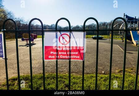Lockdown: Sign on railings of a playground for children in a park: No Entry; Play area closed due to Coronavirus: St John's Lye, Woking, Surrey