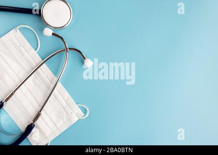 Composition with medical stethoscope, disposable face masks on a blue background. Top view. Free copy space. - Stock Photo