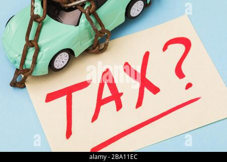 A toy car wound with a chain and a note with text. Concept on payment of transport tax - Stock Photo