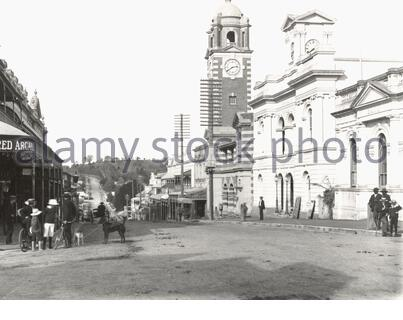 'English: Brisbane Street Ipswich, looking towards Limestone Hill. Ipswich became a city in 1904. It was going through a period of growth with coal mines, railway workshops, foundries, the woollen mill, sawmills and light industries like Roberts' Carriage Works. The quiet street belies the importance of Ipswich. The photo may have been taken on a Saturday or Sunday afternoon with all the children in the street. The clock tower belongs to the Ipswich Post Office (architect: Thomas Pye); the building to it right, also topped by a small clock tower, is the Old Town Hall.  Queensland Museum holds - Stock Photo