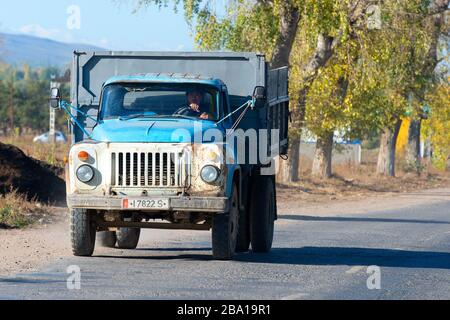 Old truck from the soviet times in Central Asia road in Karakol, Kyrgyzstan. Frontal view of lorry with rusty showing a Kyrgyz man driving. - Stock Photo