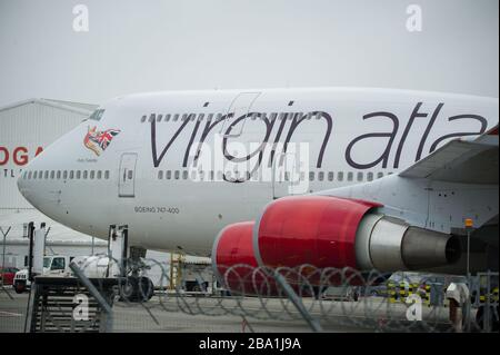 Glasgow, UK. 25th Mar, 2020. Pictured: Virgin Atlantic aircraft (Boeing 747-400 series - named Ruby Tuesday, registered G-VXLG) and an Airbus A330-200 - named Honkytonk Woman, registered G-VMIK) stand grounded on the tarmac by the Logan Air hanger. Credit: Colin Fisher/Alamy Live News