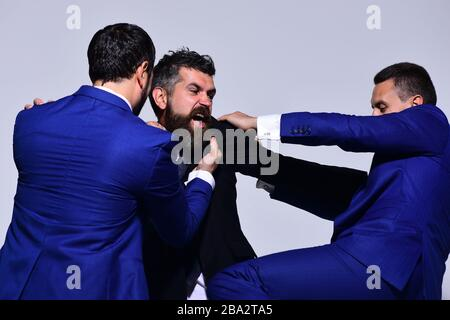 Businessmen with mad faces in formal suits on grey background. Business conflict and argument concept. Company leaders fight for business leadership. Coworkers decide upon best working position - Stock Photo