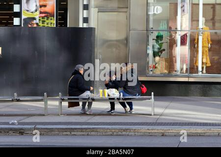New York, NY. 24th March 2020. A family dines outside on a bench in Manhattan's Upper East Side during the coronavirus COVID-19 pandemic.  An executive order issued by the Governor of New York State has prohibited restaurants and bars from serving customers except for take-out and delivery orders only. Credit: Robert K. Chin. - Stock Photo