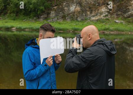 Work of photographer with model in outdoor. Photographer taking close up shot of young handsome man standing on river bank hiding part of his face beh - Stock Photo