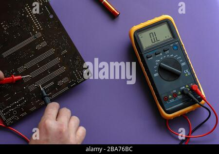 Checking the electrical resistance of the motherboard. Hands using a digital multimeter to test. View from above. Selective focus. Close-up - Stock Photo