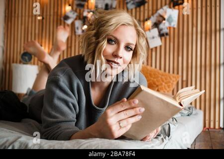Happy Woman looking to the camera, relaxing and reading book on cozy bed - Wooden wall and photos with lights - blurred background