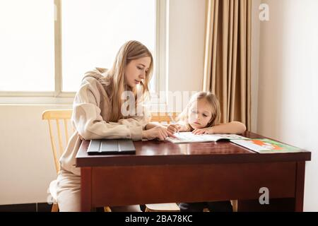 Mother helping her daughter making school homework at home. Learning at home, online learning, self quarantine, Home schooling and concept of COVID-19 - Stock Photo
