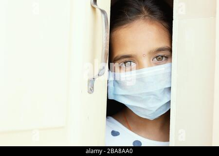 Young sad girl with medical mask wearing sneaking out through the home door - concept of home quarantine due to covid-19 or coronavirus outbreak. - Stock Photo