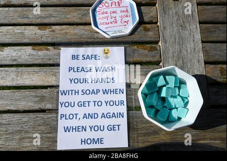 Covid19 hygiene. A container of complimentary soap with instructions to wash hands on an allotment garden during the coronavirus pandemic. - Stock Photo