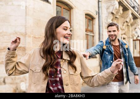 Selective focus of couple having fun while walking in city - Stock Photo