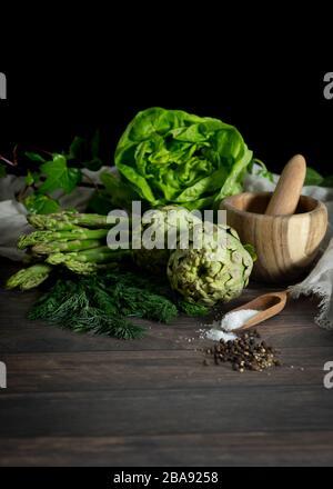 Artichokes, asparagus, herbs, salt and pepper on wooden table. Alcachofas, espárragos, lechuga, hierbas, sal y pimienta sobre mesa de madera. - Stock Photo